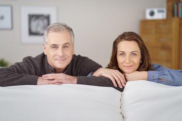 lächelndes paar schaut über das sofa