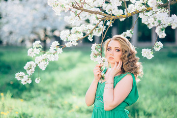 fashion beautiful blonde woman in blossoming garden of Apple trees