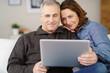 älteres paar sitzt auf dem sofa und schaut auf laptop