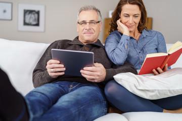 best-ager paar entspannt beim lesen auf dem sofa