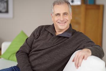 sympathischer best-ager sitzt zuhause auf dem sofa
