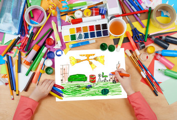 home interior, living room with toys, child drawing, top view hands with pencil painting picture on paper, artwork workplace
