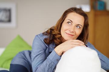 lächelnde frau sitzt entspannt auf dem sofa