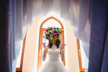 bride throws  into the air colored bouquet of flowers