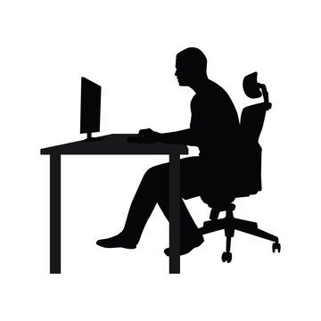 Man sitting on office chair at table and working on computer. Si