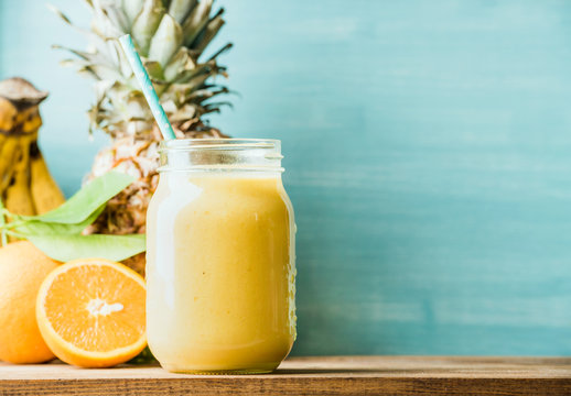Freshly blended yellow and orange fruit smoothie in glass jar with straw