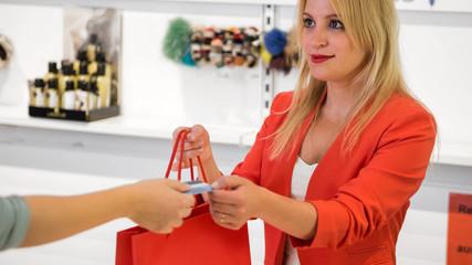 Einzelhandel - Blonde Verkäuferin nimmt Kreditkarte entgegen