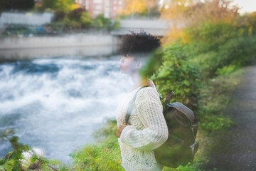 Double exposure of young handsome african curly black hair woman outdoor in the city and nature - artistic concept