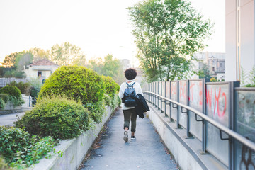 Rear view of young handsome african curly black hair woman outdoor in the city wearing backpack walking outdoor in the city - traveling, commute, leaving concept