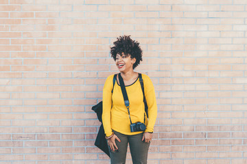 Knee figure of young handsome african curly black hair woman posing leaning against a wall, overlooking laughing - serene, carefree, happiness concept