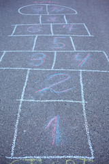 Hopscotch drawn on asphalt. Soft focus on number 1