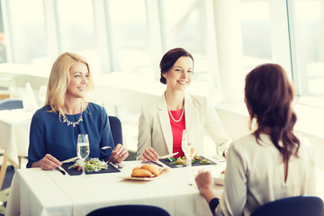 happy women eating and talking at restaurant