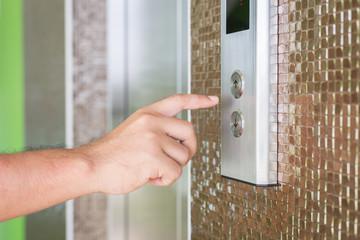 Hand pressing silver elevator button