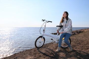 девушка со своим велосипедом остановилась на отдых на берегу залива