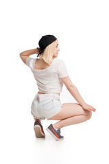 Female model in tshirt and shorts squating on haunches isolated