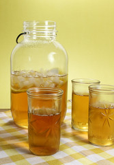 Three fruit jar glasses with ice tea. In the background a vintage mason jar contains iced tea.