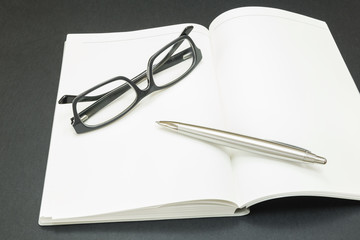 book with glasses and a pen on a black background