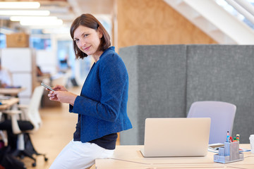 Businesswoman at her desk in open office typing on phone