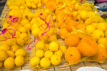 Oranges and lemons in bags at market
