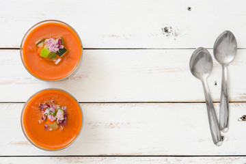 Gazpacho soup and ingredients on white wooden background