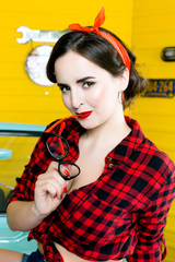 Young Woman With Pinup Hair Style And Makeup Posing on blue retro car background wearing eyeglasses