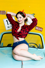 Young Woman With Pinup Hair Style And Makeup Posing on blue retro car