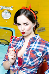 Portrait of Young Woman With Pinup Hair Style And Makeup holding candy in hand and  Posing In Retro Studio