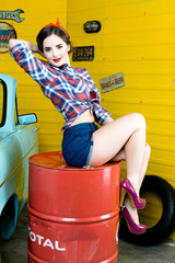 Young Woman With Pinup Hair Style And Makeup Posing In Retro Studio