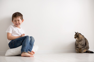 the boy plays with a cat of the house