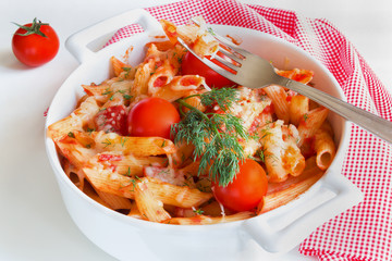 Pasta (penne) in white pan on white table. Vegetarian, cooked with tomatoes, garlic and cheese.