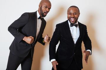 two afro-american businessmen in black suits emotional posing, gesturing, smiling. wearing bow-ties
