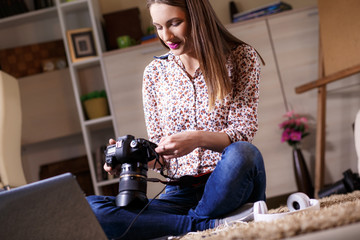 Young female photographer with laptop using modern dslr photo camera. Home interior.