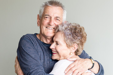 Older man and woman hugging each other and smiling