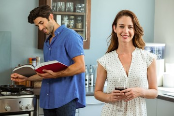 Woman holding wine glass and man cooking with recipe book