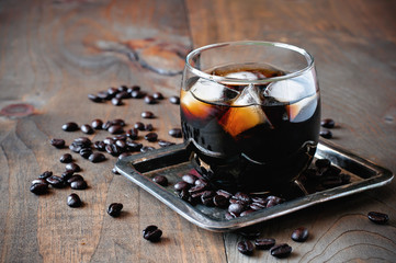 Kahlua liqueur in glasses with coffee beans on a wooden background, selective focus