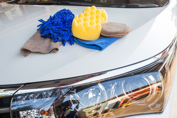 Yellow, green sponges and blue mitts for washing and microfiber fabric with cleaner cloth on white car