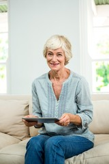 Portrait of smiling senior woman with digital tablet