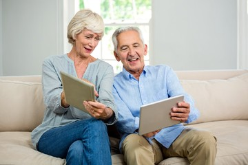 Smiling senior couple using digital tablet at home