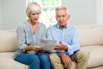 Sad senior couple reading document at home