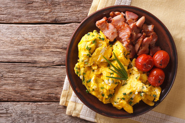 Breakfast is scrambled eggs with chives, fried bacon closeup. Horizontal top view