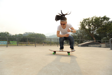 skateboarding woman practice ollie at skatepark