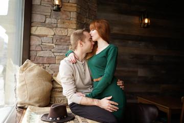 Portrait of hugging couple on window sill