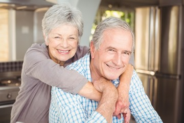 Portrait of cheerful senior couple embracing in kitchen