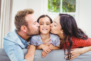Mother and father kissing daughter at home