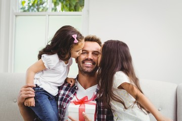 Father holding gift box and daughters kissing him