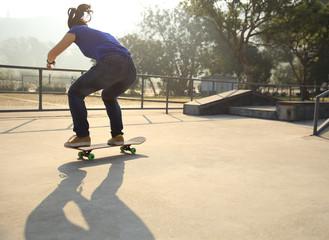 skateboarding woman practice ollie at skatepark