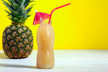 glass bottles with juice and pineapple on wooden table on yellow background