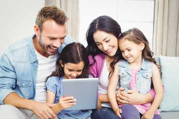 Family smiling while looking in digital tablet