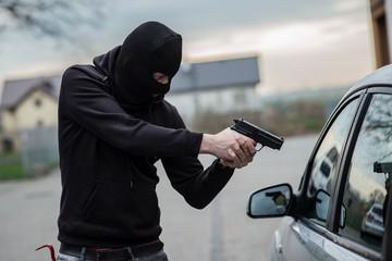 car thief pointing a gun at the driver
