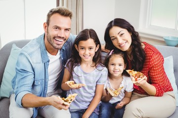 Happy family eating pizza while sitting on sofa